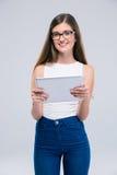 Adolescente femenino sonriente en los vidrios que llevan a cabo cálculo de la tableta Imagen de archivo libre de regalías