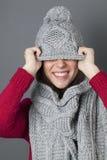 Adolescente femenino sonriente que bromea en la ocultación debajo del sombrero del invierno Foto de archivo libre de regalías