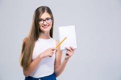 Adolescente femenino sonriente que muestra el cuaderno en blanco Foto de archivo