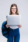 Adolescente femenino sonriente que se coloca con el ordenador portátil Fotografía de archivo