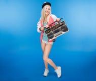 Adolescente femenino sonriente que sostiene el equipo estéreo portátil retro Fotos de archivo