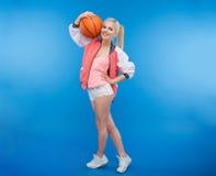 Adolescente femenino sonriente que sostiene la bola del baloncesto Imagen de archivo