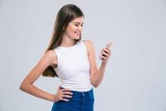 Adolescente femenino sonriente que usa smartphone Imagen de archivo