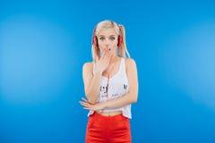 Adolescente femenino sorprendente en las auriculares que miran la cámara Fotografía de archivo