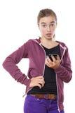 Adolescente femenino sorprendido con el teléfono elegante Imágenes de archivo libres de regalías