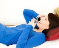 Adolescente femenino sorprendido que telefona en un sofá Foto de archivo