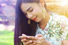 Adolescente femenino tan lindo usando smartphone feliz en parque Imagen de archivo libre de regalías