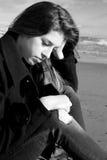 Adolescente femenino triste que se sienta delante del océano Foto de archivo libre de regalías