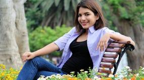 Adolescente femenino y felicidad que se sientan en parque Fotografía de archivo libre de regalías