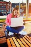 Adolescente femminile affascinante che si siede sul banco di parco con il computer portatile Fotografia Stock
