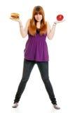 Adolescente femminile che decide fra l'hamburger o A Fotografia Stock