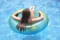Adolescente femminile che galleggia sul galleggiante in stagno Immagini Stock Libere da Diritti
