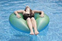 Adolescente femminile che galleggia sul galleggiante in stagno Fotografie Stock Libere da Diritti