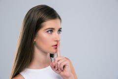 Adolescente femminile che mostra dito sopra le labbra Fotografia Stock Libera da Diritti