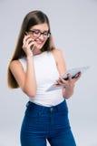 Adolescente femminile che parla sul telefono e che per mezzo del computer della compressa Immagini Stock