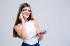Adolescente femminile che parla sul telefono e che per mezzo del computer della compressa Fotografie Stock