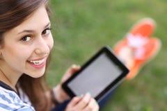 Adolescente femminile che per mezzo del ridurre in pani digitale Fotografie Stock