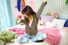 Adolescente femminile che sbadiglia sedendosi a letto di mattina panoramica stanca Immagini Stock