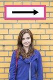 Adolescente femminile che sta nell'ambito di un segnale di direzione Immagini Stock Libere da Diritti