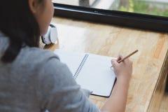 adolescente femminile della ragazza asiatica che si trova sul pavimento e che scrive parola & x22; I l Fotografie Stock