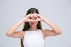 Adolescente femminile felice che mostra il gestur del cuore Fotografia Stock
