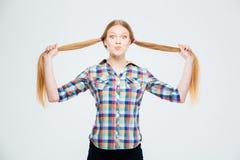 Adolescente femminile felice che tiene le sue code di cavallo Fotografie Stock
