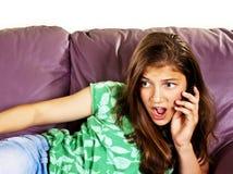Adolescente femminile sorpreso che comunica sul telefono Fotografia Stock