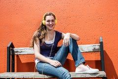 Adolescente femminile sorridente che ascolta la musica in sue cuffie variopinte Immagine Stock