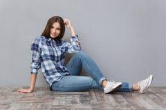 Adolescente femminile sorridente che si siede sul pavimento Immagine Stock