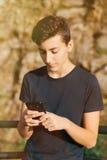 Adolescente fresco con cincuenta años y un móvil Imagen de archivo