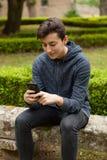 Adolescente fresco con cincuenta años y un móvil Fotografía de archivo libre de regalías