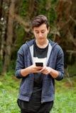 Adolescente fresco con cincuenta años y un móvil Imágenes de archivo libres de regalías