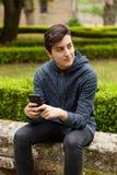 Adolescente fresco con cincuenta años y un móvil Fotos de archivo