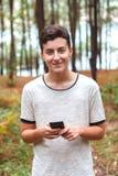 Adolescente fresco con dieciséis años y un móvil Imagenes de archivo