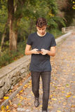 Adolescente fresco con un móvil en la calle Foto de archivo