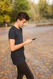Adolescente fresco con un móvil en la calle Fotografía de archivo