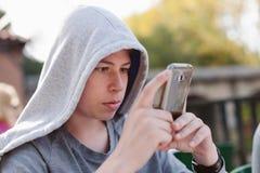 Adolescente fresco con un móvil en la calle Imagenes de archivo