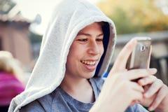 Adolescente fresco con un móvil en la calle Foto de archivo libre de regalías