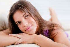 Adolescente fresco feliz que pone en el sofá del th Fotografía de archivo