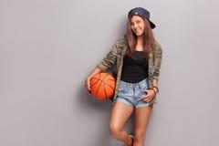 Adolescente fresco que lleva a cabo un baloncesto Foto de archivo libre de regalías