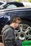 Adolescente fresco que se sienta delante de un borde de la rueda Imagenes de archivo