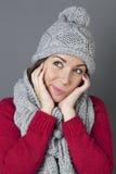 Adolescente fresco que sonríe en el pensamiento en saludos estacionales del invierno Foto de archivo libre de regalías