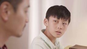 Adolescente frustrado asiático que empaña a su padre en casa almacen de metraje de vídeo
