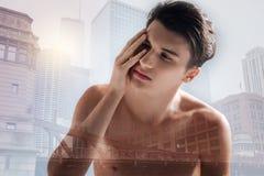 Adolescente frustrado que toca su cara con una mano Imagenes de archivo