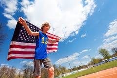 Adolescente, ganador de la raza, corriendo con la bandera de los E.E.U.U. Imagen de archivo