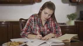 Adolescente grazioso che fa il suo compito che si siede a casa alla tavola La scolara che riscrive il testo dal libro a archivi video