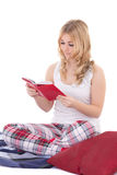 Adolescente grazioso in pigiami che si siedono e libro di lettura isolato Fotografia Stock
