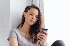 Adolescente grazioso triste con mandare un sms dello smartphone Fotografie Stock