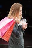 Adolescente hacia fuera para hacer compras, sosteniendo las bolsas de papel y el batido de leche Imágenes de archivo libres de regalías