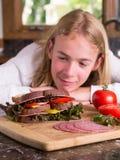 Adolescente hambriento que mira un emparedado grande Fotos de archivo
